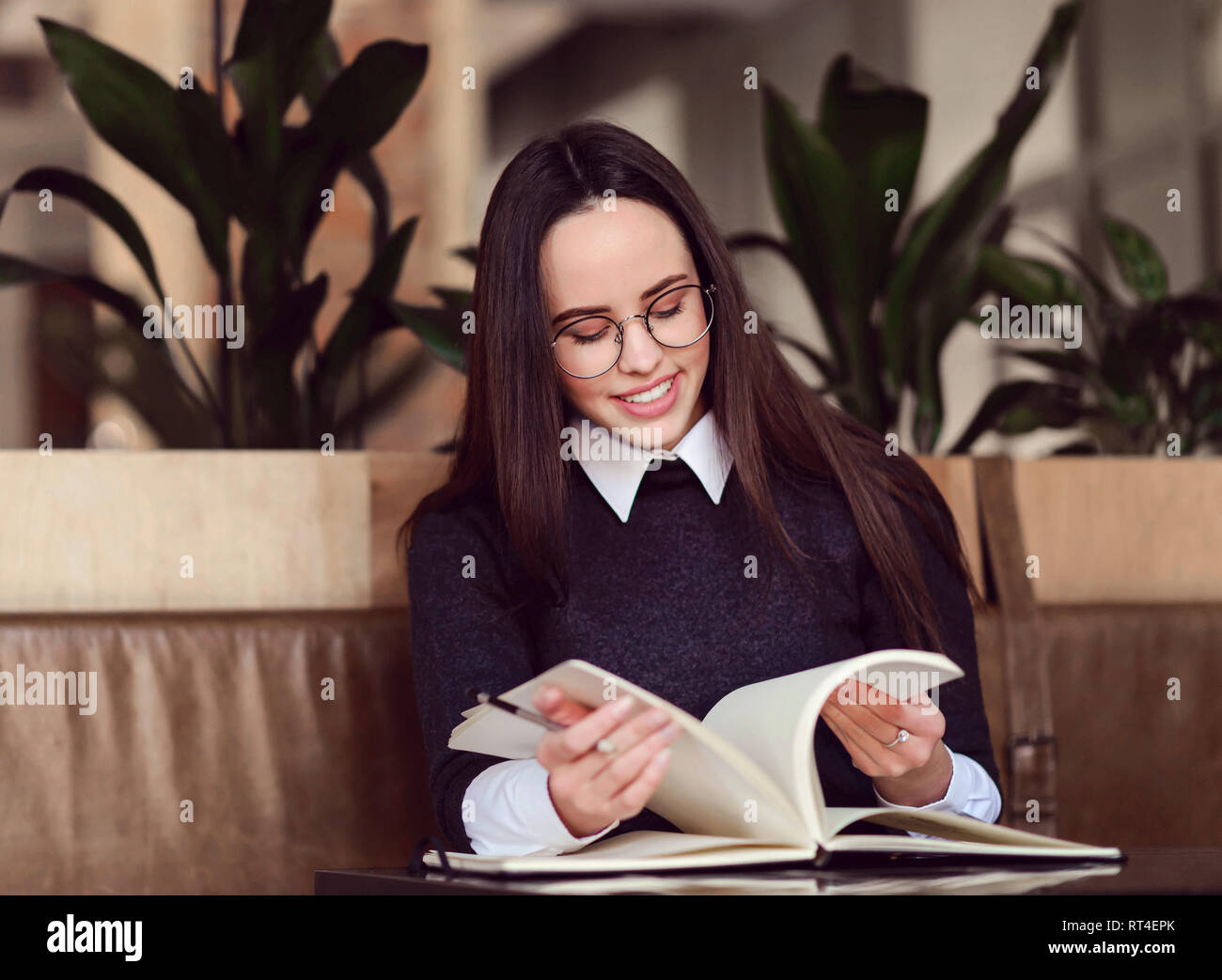 Cheerful girl in eyewear leafing through a notebook and searching sommething in it - Stock Image