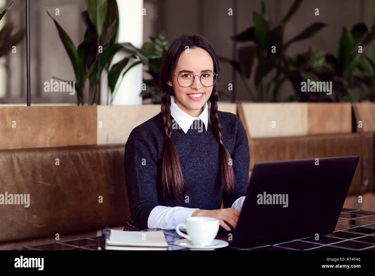 Schoolgirl with braids typing something and researching on the laptop at the cafeteria Stock Photo