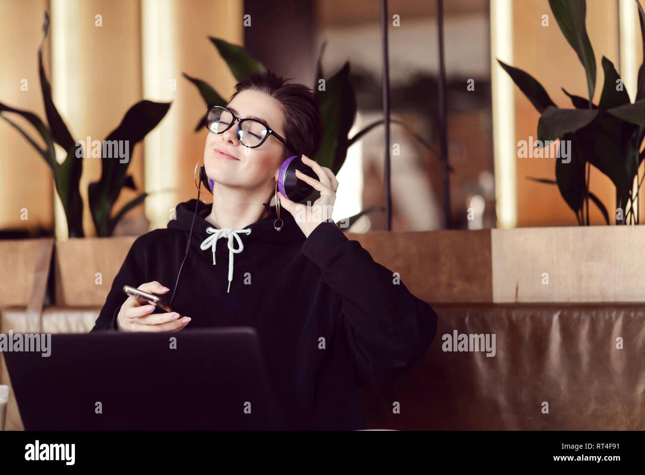 Shorthair hipster girl in eyewear wearing black hoody enjoying music while sitting at the cafe - Stock Image