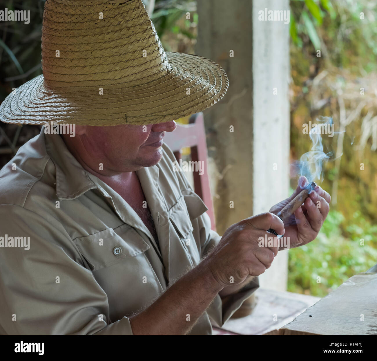 A tobacco grower inspects a lit cigar in Viñales Cuba. - Stock Image