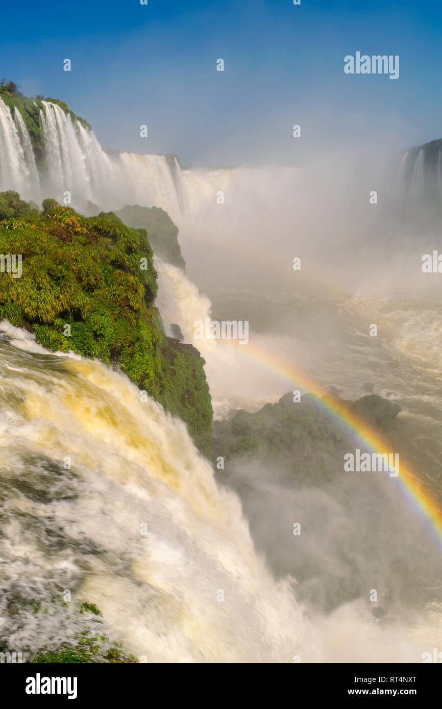 The Devil's Throat waterfall in Iguazu Falls with a rainbow in the foreground. - Stock Image