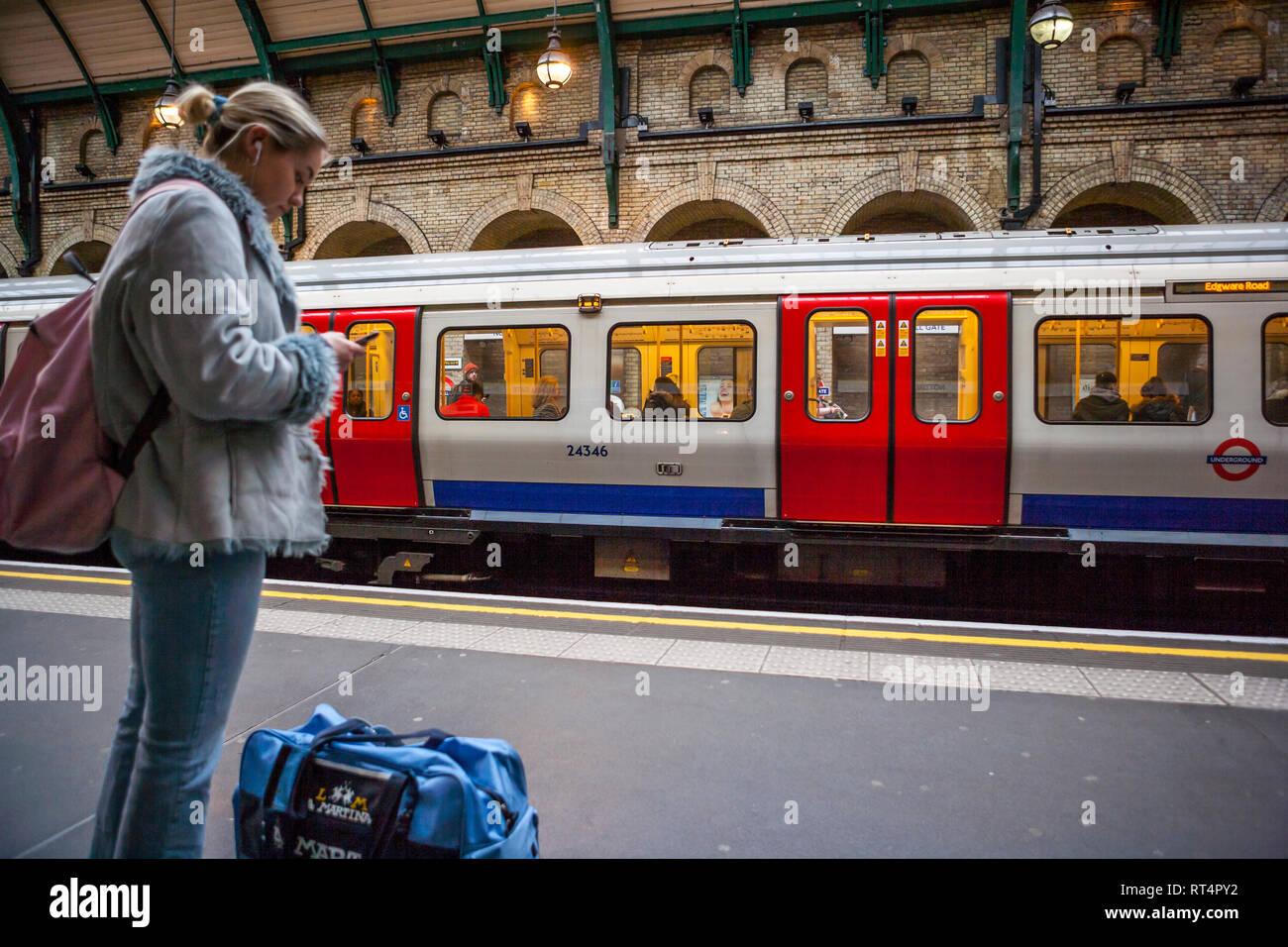 Waiting on Notting Hill Gate tube station platform, London - Stock Image