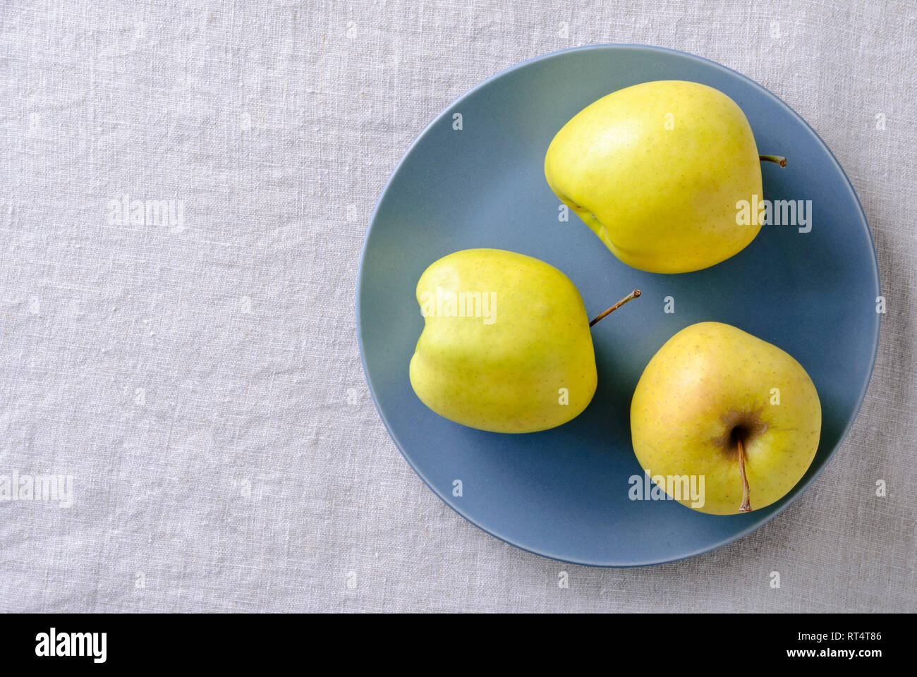 Ugly fresh food concept with fresh misshapen golden apples on a blue plate in a concept of aesthetic perceptions of food, top down on white with copy  - Stock Image
