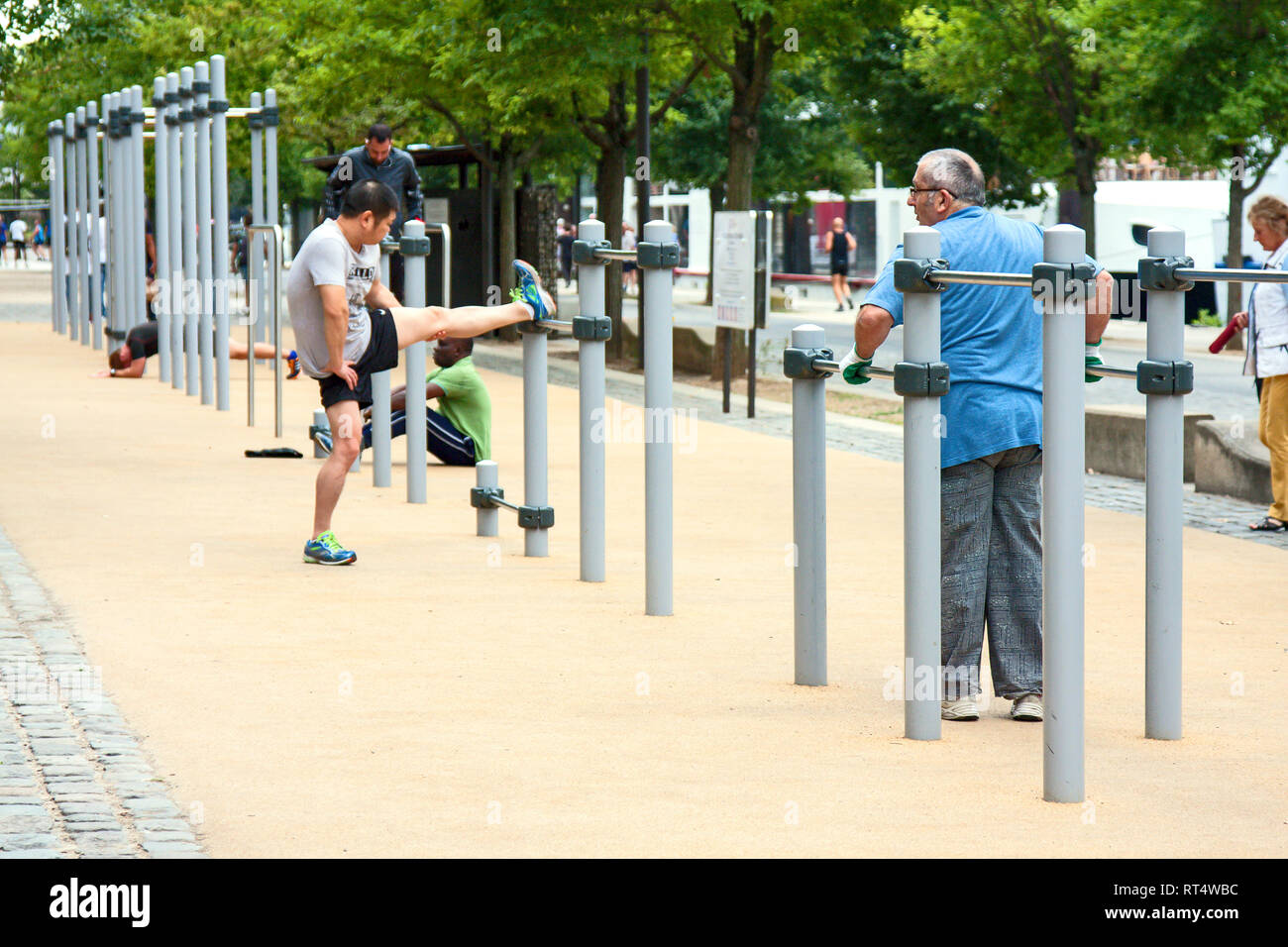 outdoor exercise center; men working out; health; fitness; strength; physical effort, Lyon; France; summer; horizontal - Stock Image