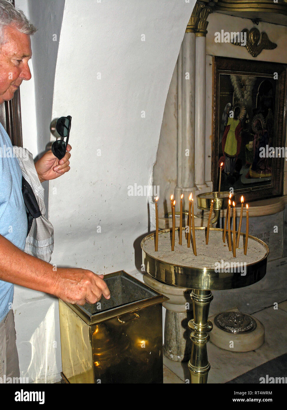 visitor lighting candle, Church of Annuciation, miraculous icon found,1833, Greek Orthodox, religious practise, pray, Hora, Cyclades, Tinos, Greece, E Stock Photo