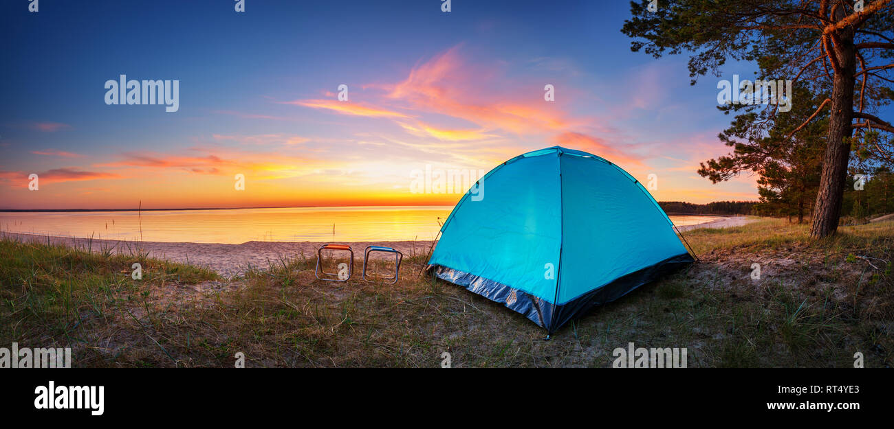 Family resting with tent in nature at sunset - Stock Image