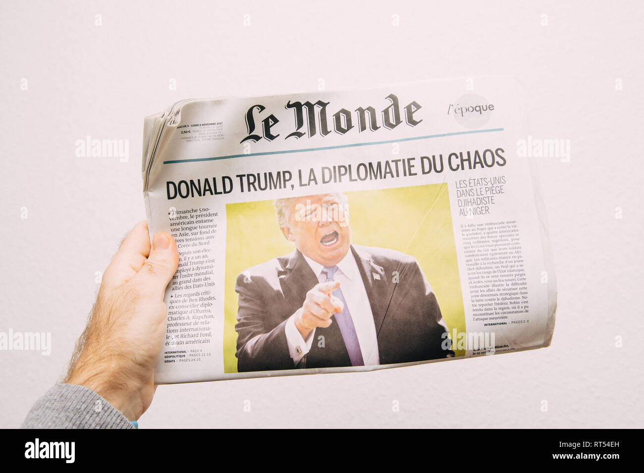 PARIS, FRANCE - NOV 6, 2017: Male hand holding against white background latest Le Monde newspaper featuring headline Donald Trump is Chaos Diplomacy - Stock Image