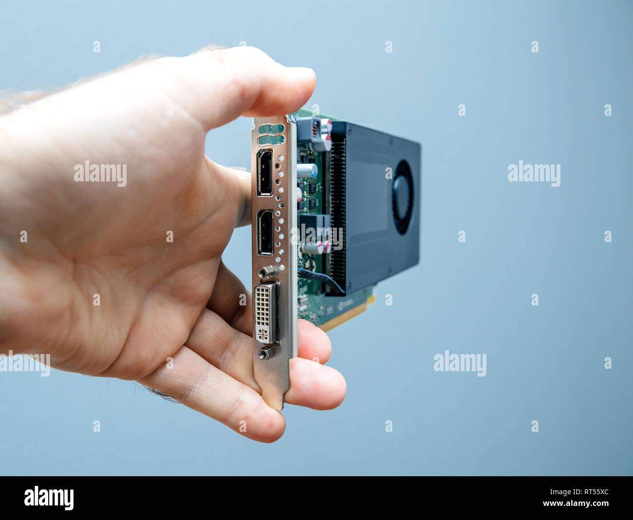 Man holding against gray background powerful GPU video card  used in professional video production in bitcoin cryptocurrency mining - Stock Image