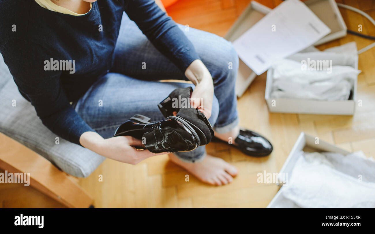 View rom above of young woman unboxing unpacking several pairs of new shoes bought via online store demonstration showing them  - Stock Image