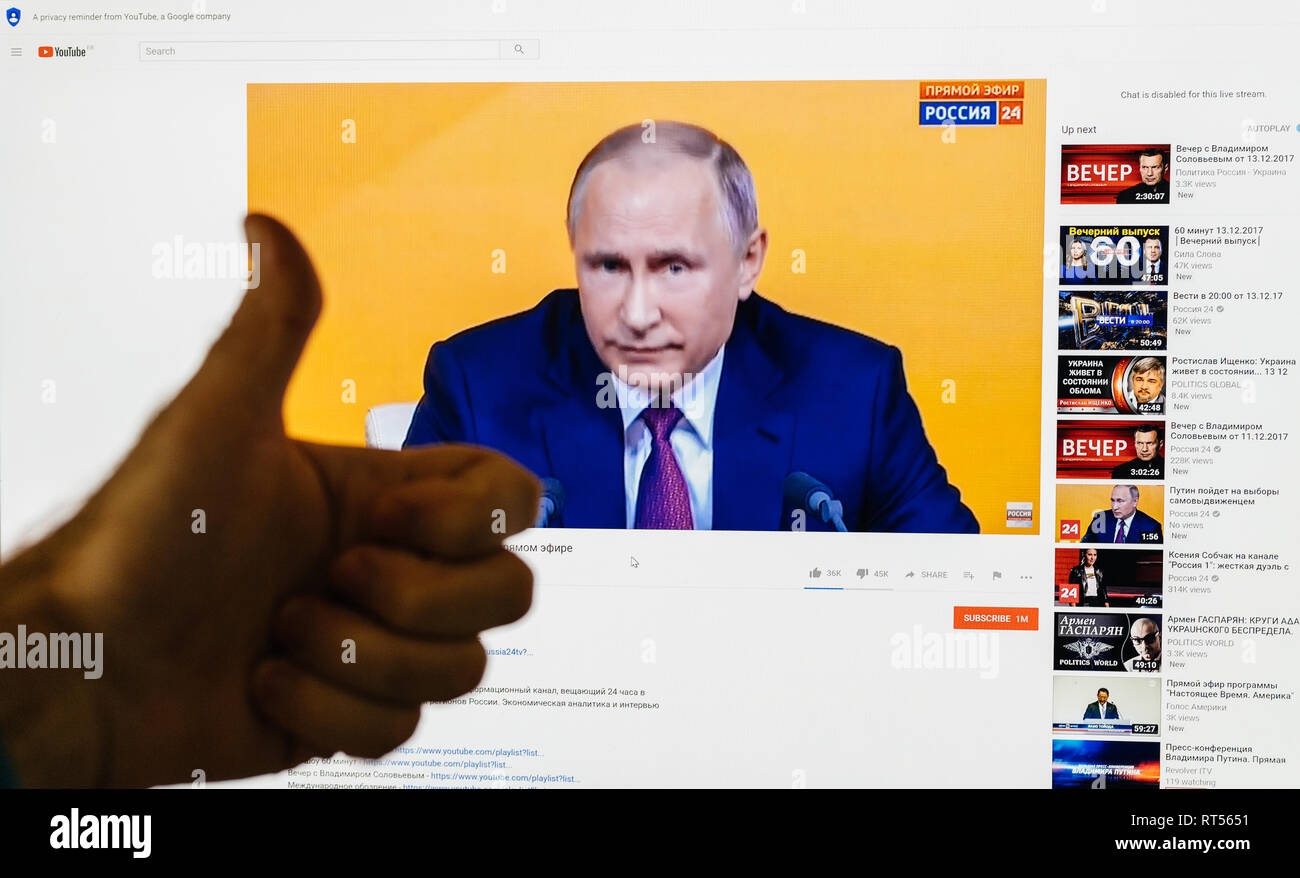 PARIS, FRANCE - DEC 14, 2017: Man thumb up for the Russian President - watching on Youtube live channel of Rossiya RTR the Russian President Vladimir Putin give final media Q&A before March election - Stock Image