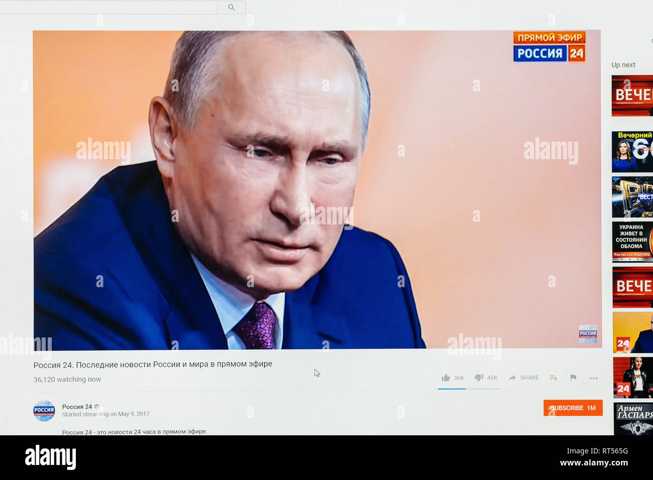PARIS, FRANCE - DEC 14, 2017: Man watching on Youtube live channel of Rossiya RTR the pensive Russian President Vladimir Putin give final media Q&A before March election - Stock Image