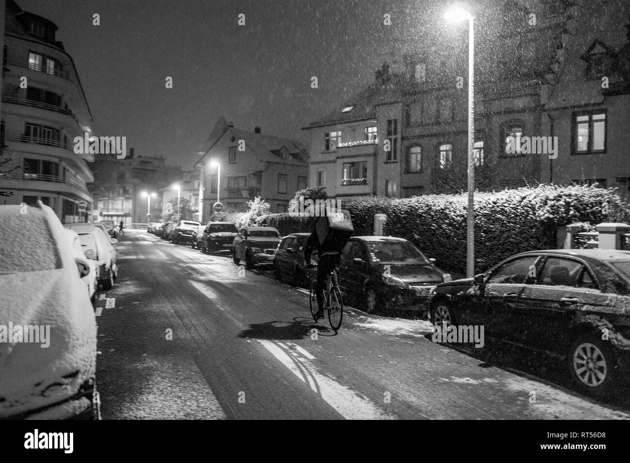 STRASBOURG, FRANCE - DEC 3 2017: Deliveroo delivery bike in French city cycling fast for food delivery on time on a cold winter snowy night in residential neighborhood - Stock Image