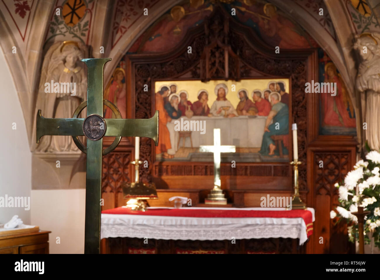 High altar in a church with large brass cross in the foreground - Stock Image