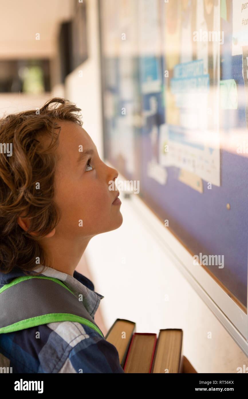 Schoolboy looking at noticeboard in the corridor - Stock Image