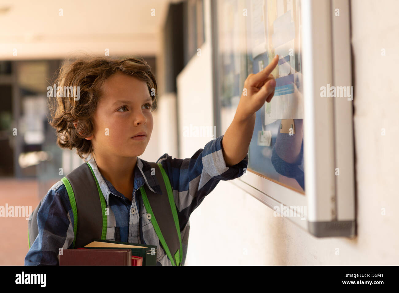 Schoolboy pointing at noticeboard in the corridor - Stock Image