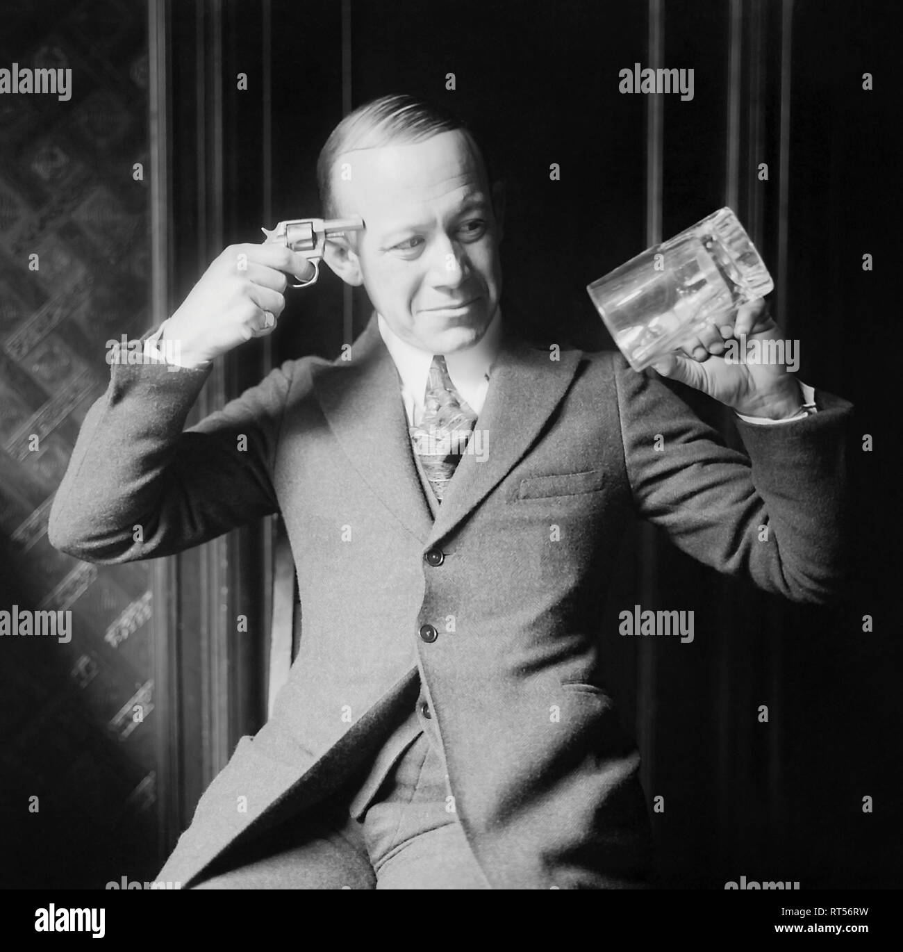 Ernie Hare holding an empty mug and a pistol against his head, displaying his distaste for prohibition laws. - Stock Image