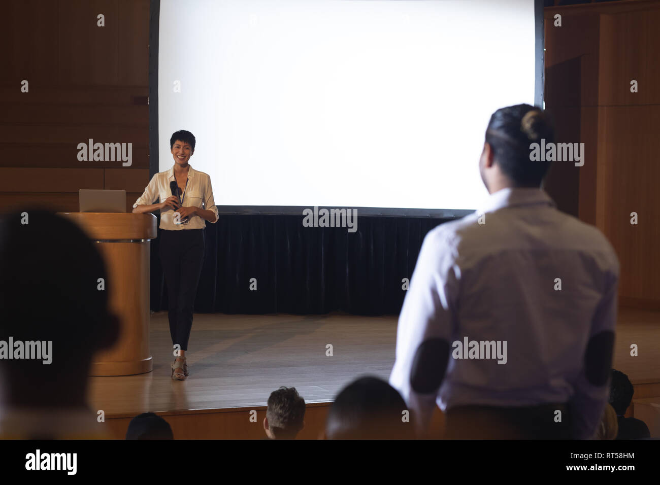 Woman from the audience standing and asking query in the auditorium - Stock Image