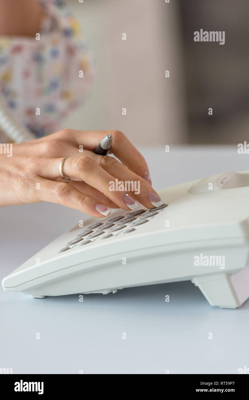 Closeup of female hand dialing telephone number using white landline phone. - Stock Image