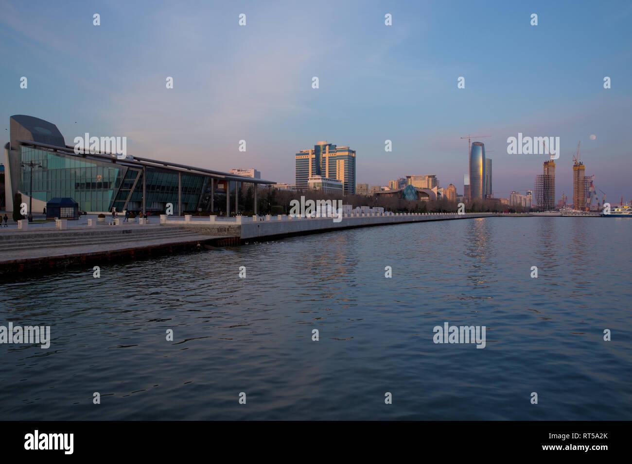 Baky skyline view from Baku boulevard the Caspian Sea embankment . Tall buildings in Baku. Ship cranes . Moon Baku Business Center Stock Photo