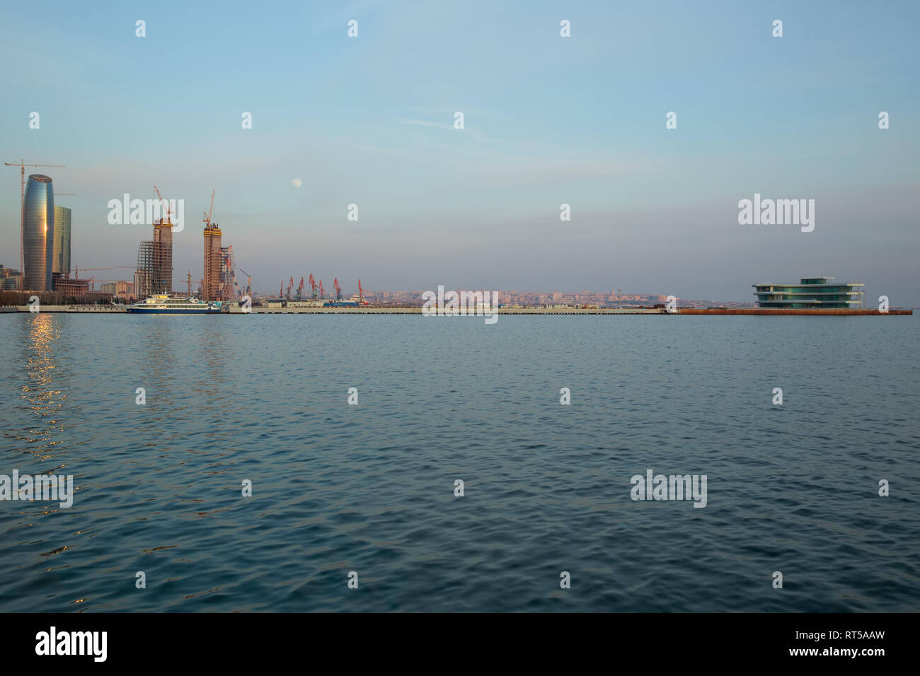 Baky skyline view from Baku boulevard the Caspian Sea embankment . Tall buildings in Baku. Ship cranes . Moon. harbor . Port Stock Photo