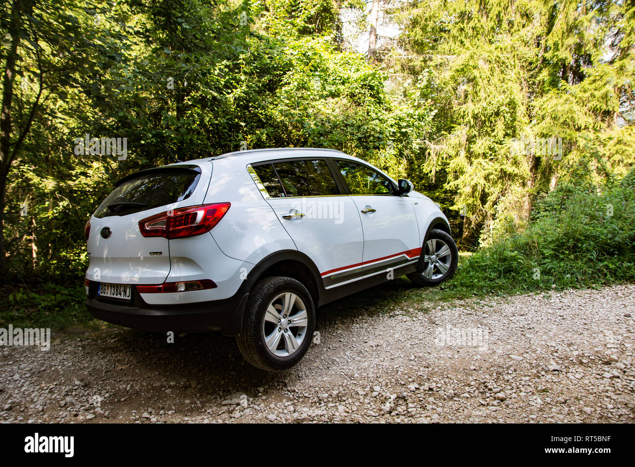 Kia Sportage 2.0 CRDI awd or 4x4, white color, stuck on a trench on a Tara mountain near lake Zaovine, with one wheel in the air, and others on grass. Stock Photo
