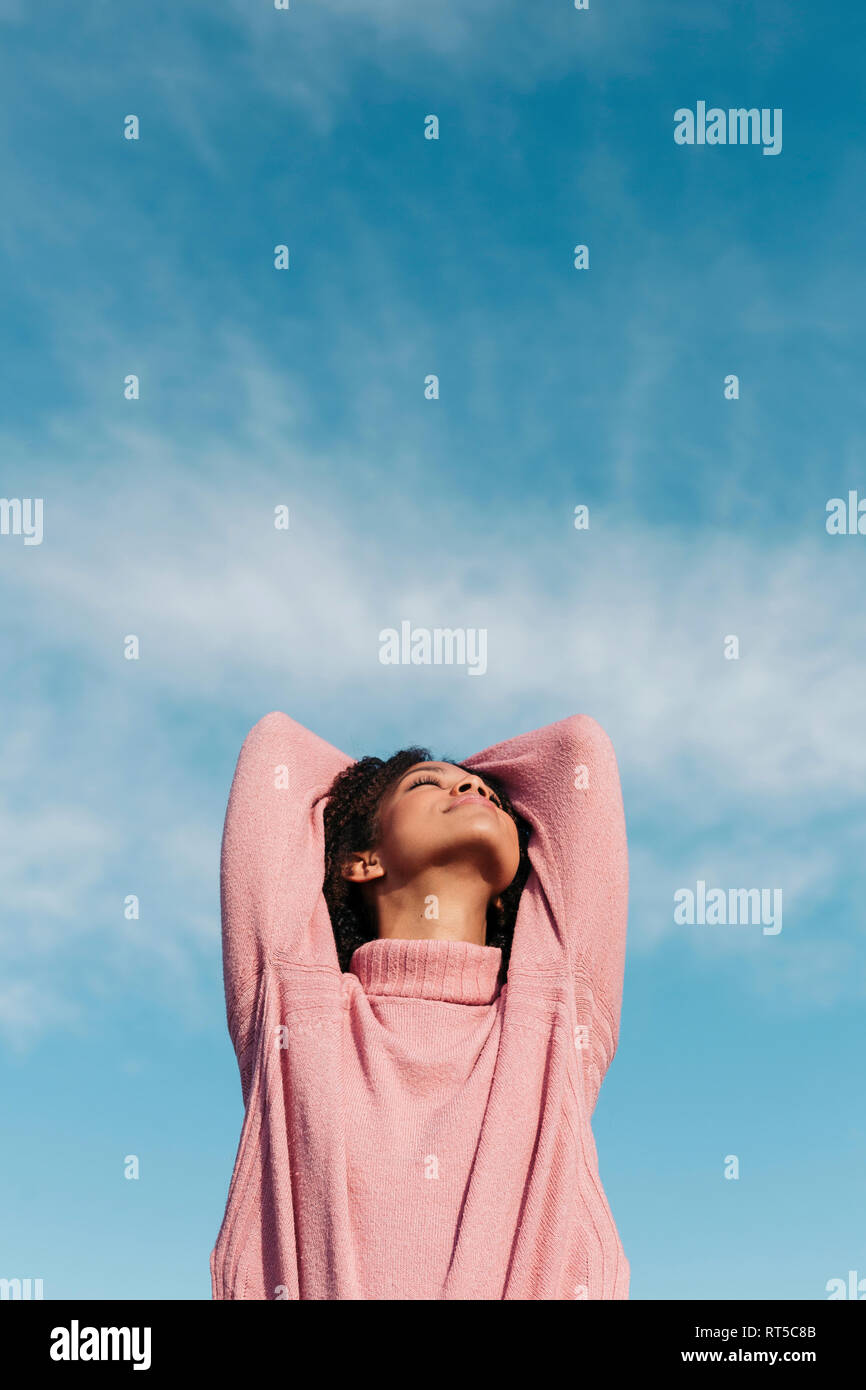 Relaxed young woman wearing pink turtleneck pullover enjoying fresh air - Stock Image