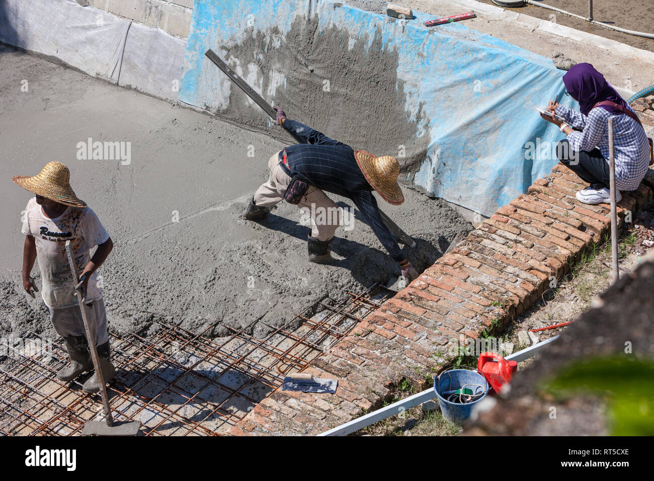 Young Malaysian Woman Supervising Laborers Laying Cement Floor, Fort Cornwallis, George Town, Penang, Malaysia - Stock Image