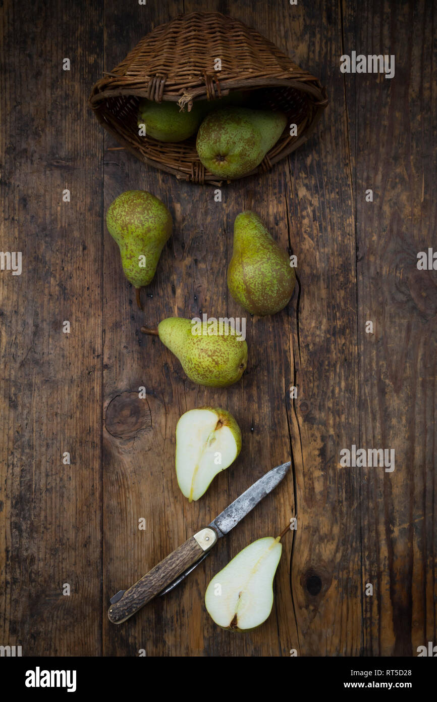 Whole and sliced organic pears 'Conference' with pocket knife on dark wood - Stock Image