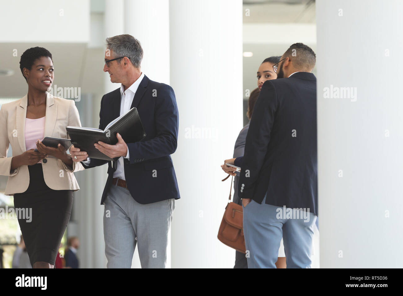 Diverse business people interacting with each other while walking in lobby office Stock Photo