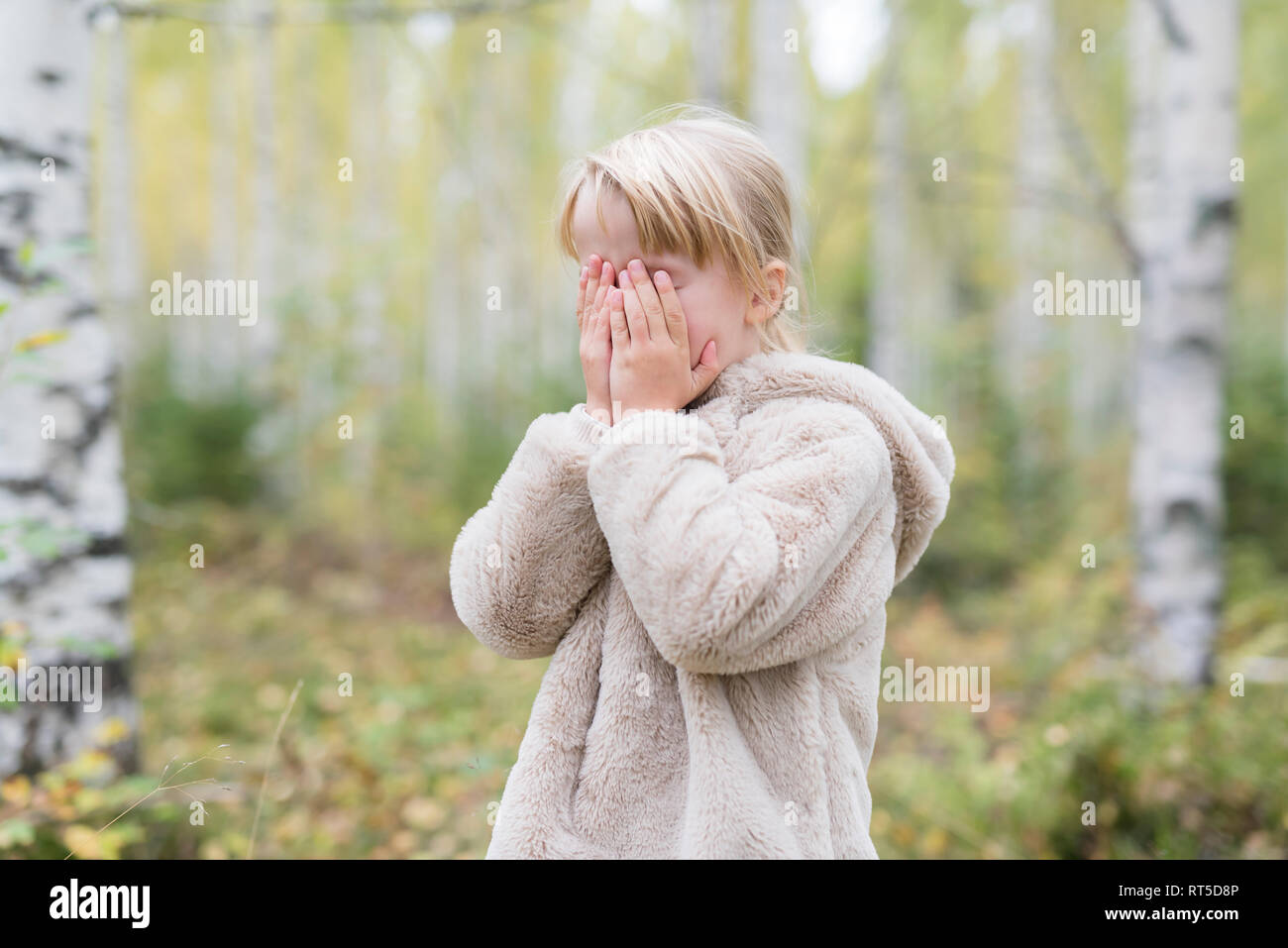 Blond girl playing Hide and Seek in a forest - Stock Image