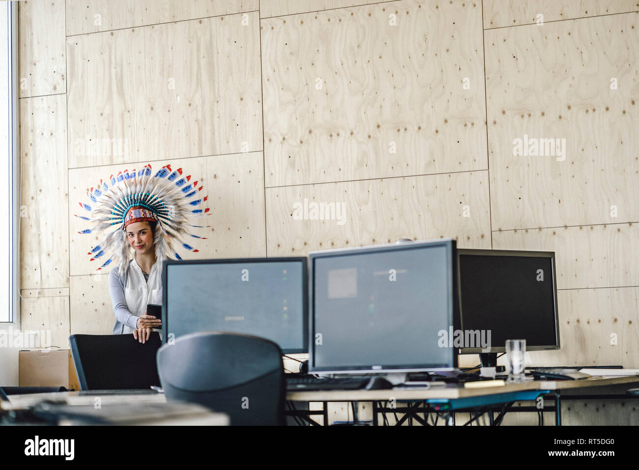 Young woman wearing Indian headdress, standing in office - Stock Image