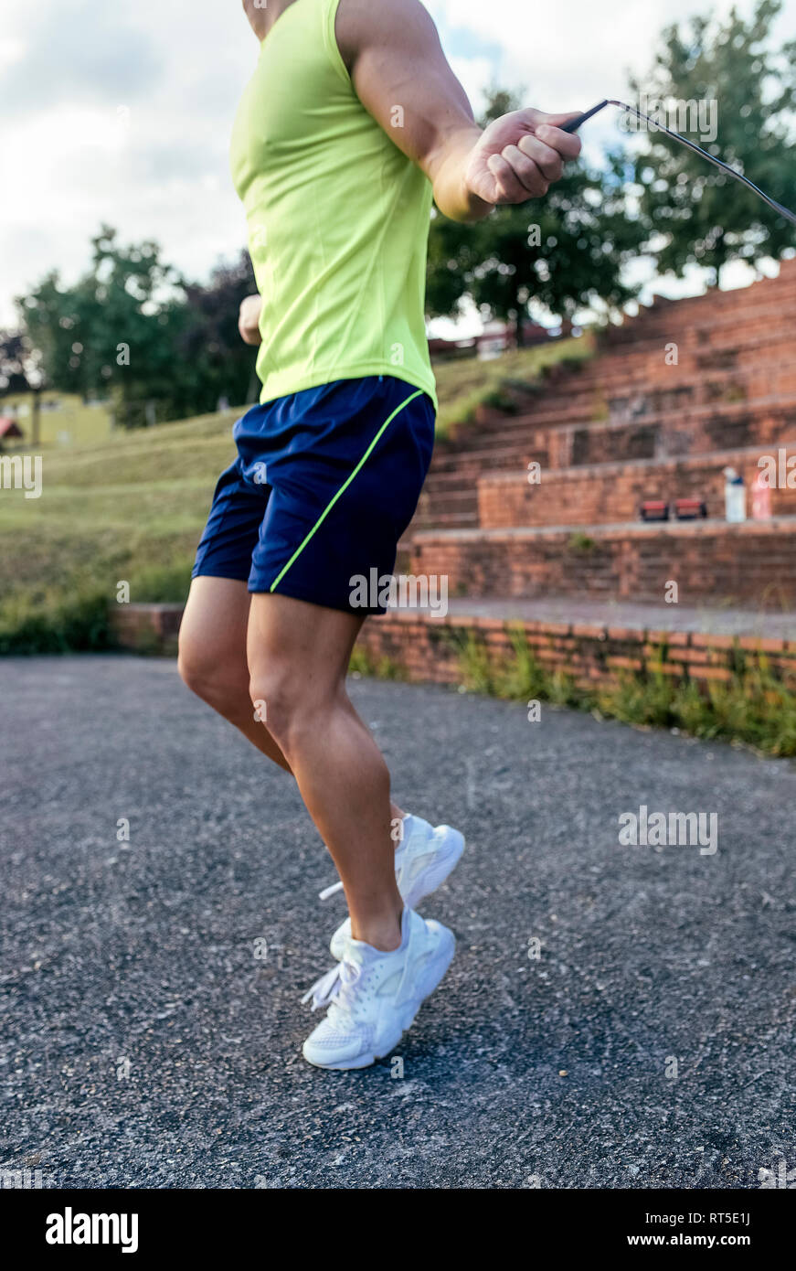 Close-up of muscular man skipping rope outdoors - Stock Image