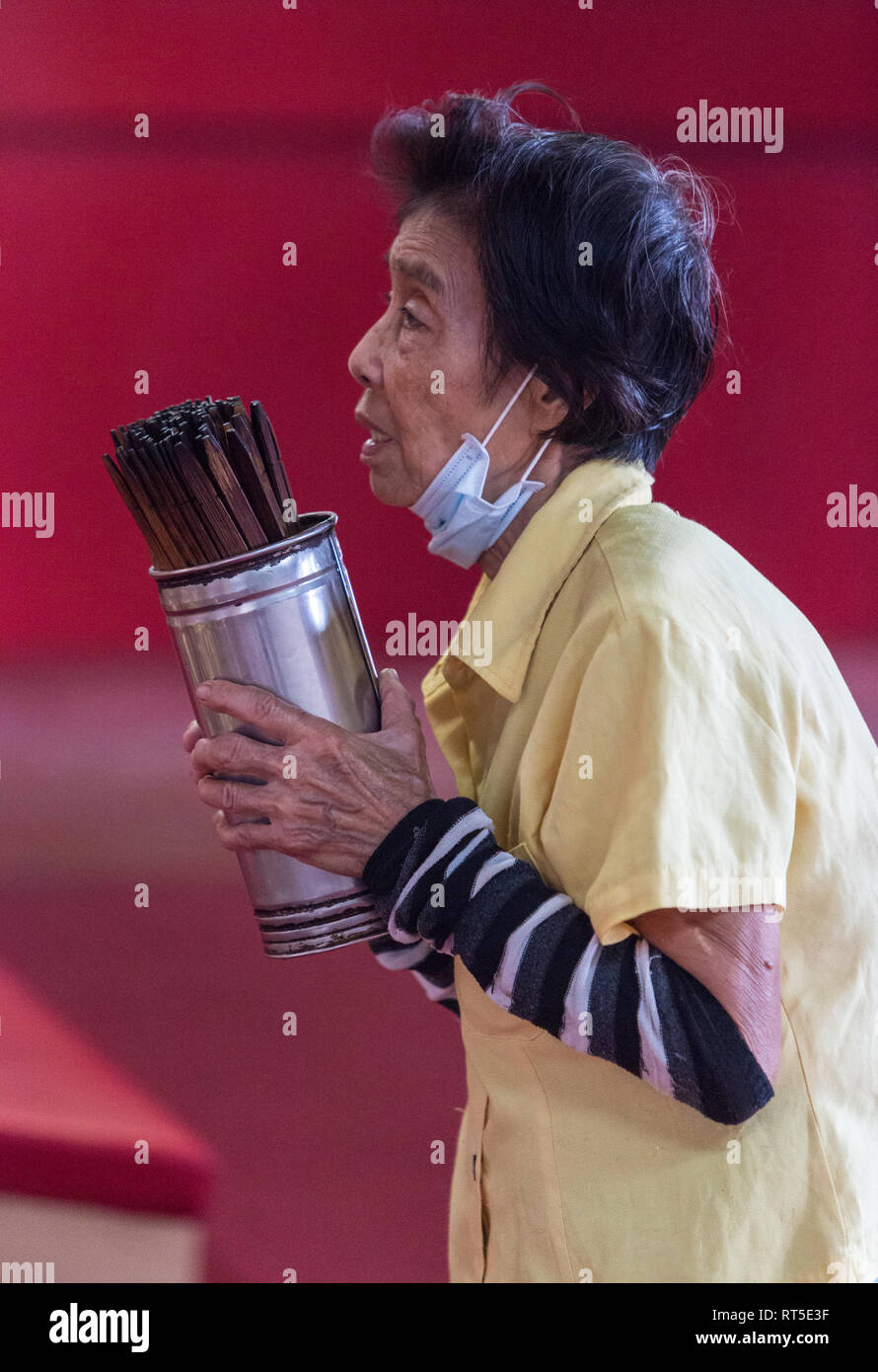 George Town, Penang, Malaysia.  Worshiper with Chinese Fortune Sticks in Goddess of Mercy Temple, Kuan Yin Teng, Kong Hock Keong. - Stock Image