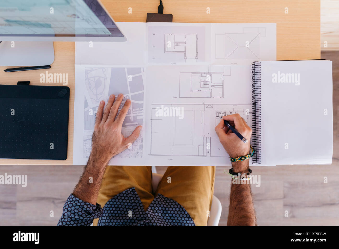Close-up of architect working at home on floor plan - Stock Image