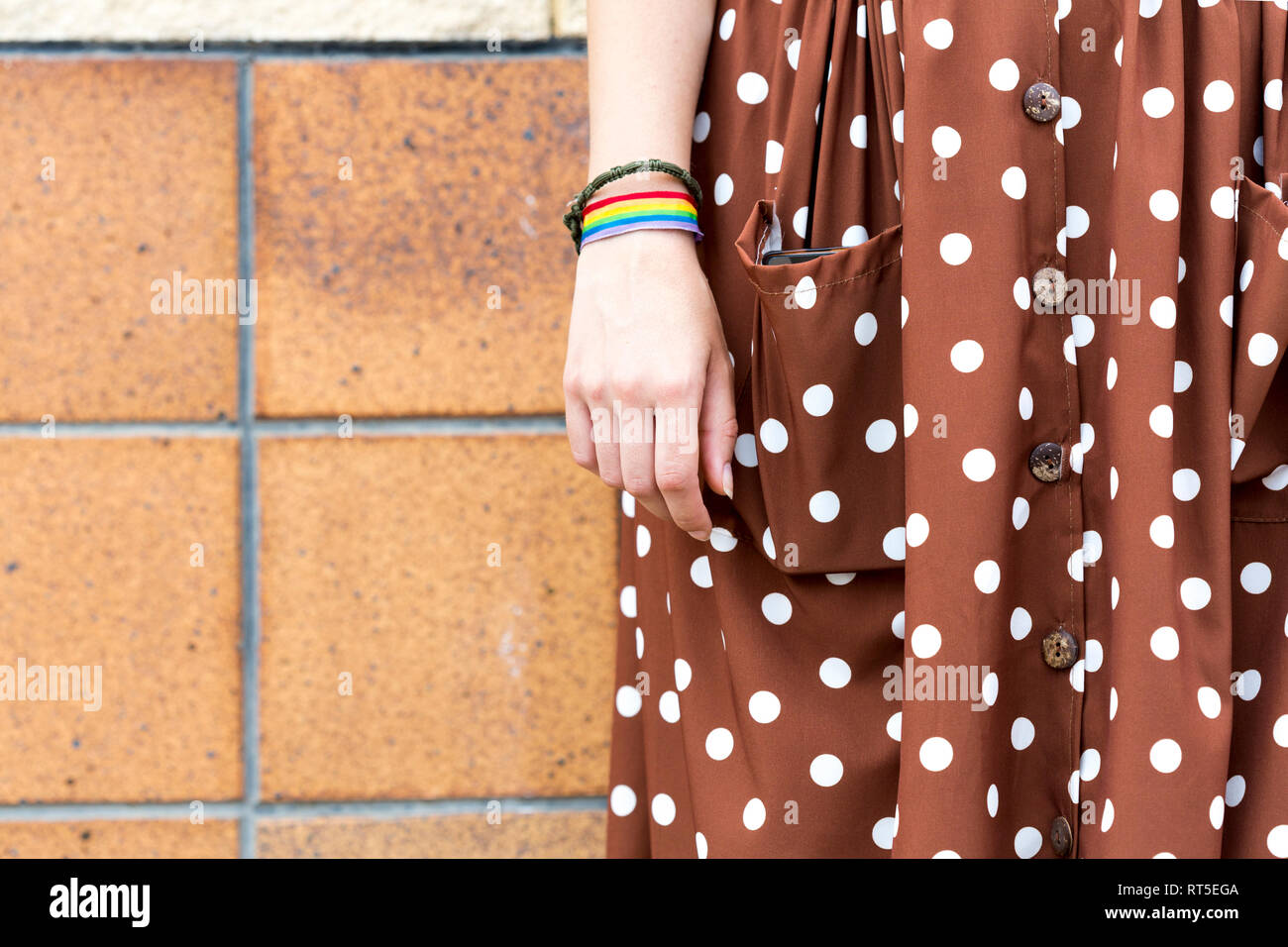 Young woman wearing brown dress with white polka dots and wristband with prismatic colours, partial view - Stock Image