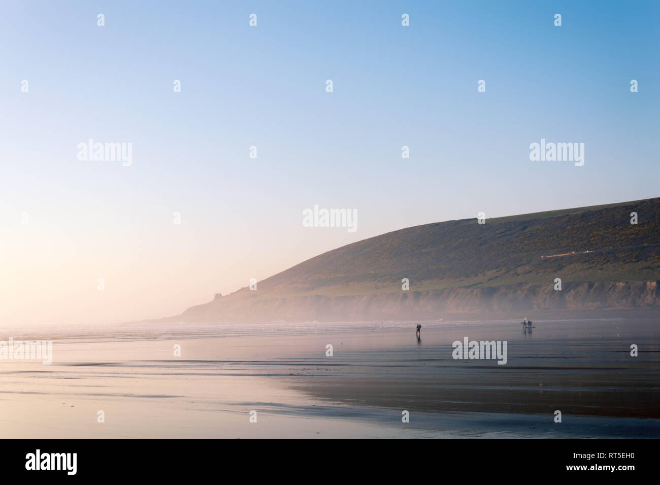 surfers silhouetted walking on the beach at sunset on a warm February day 2019. Saunton Sands, Devon, UK. 27th feb 2019. - Stock Image