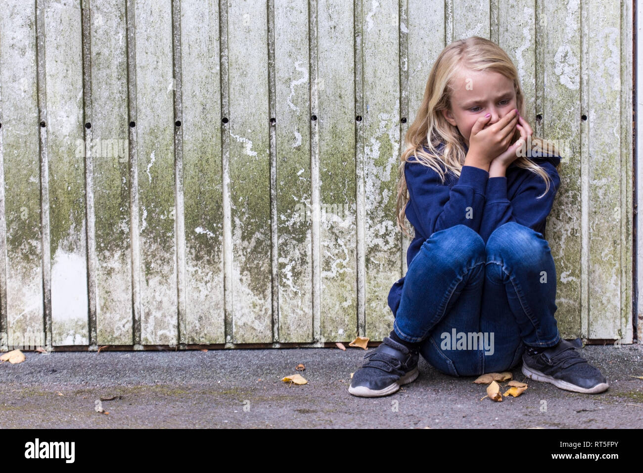 Frightened girl crouching in front of wooden wall - Stock Image
