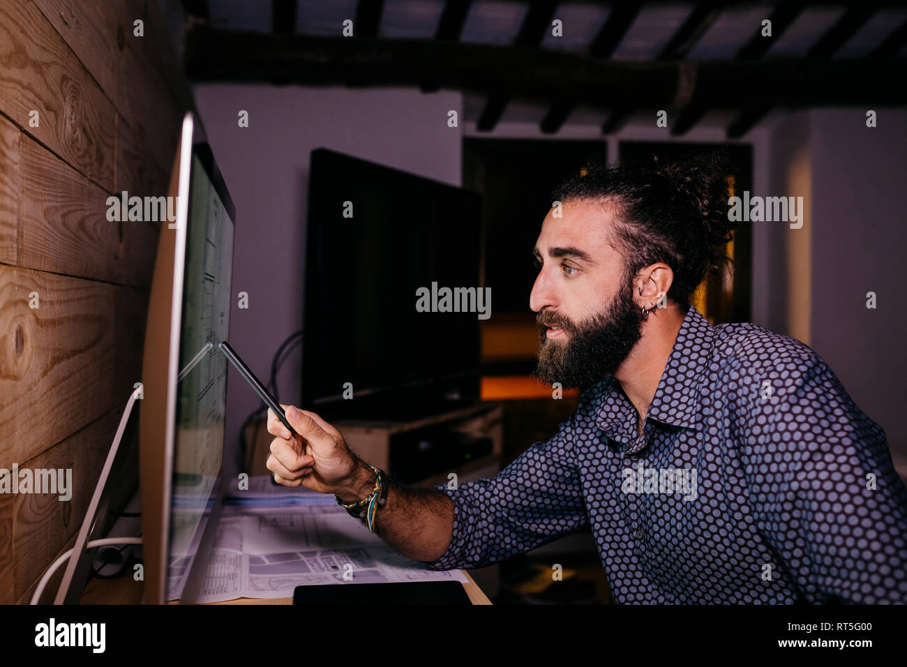 Young architect working hard on a new project at home at night - Stock Image