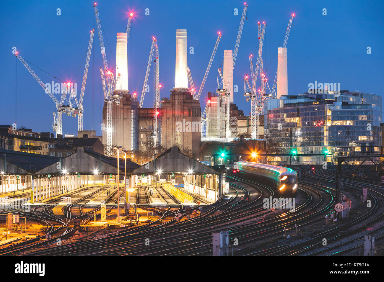United Kingdom, England, London, view of railtracks and trains in the evening, former Battersea Power Station and cranes in the background - Stock Image