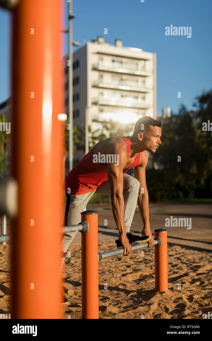 Fit man working out in climbing parcour, stretching - Stock Image