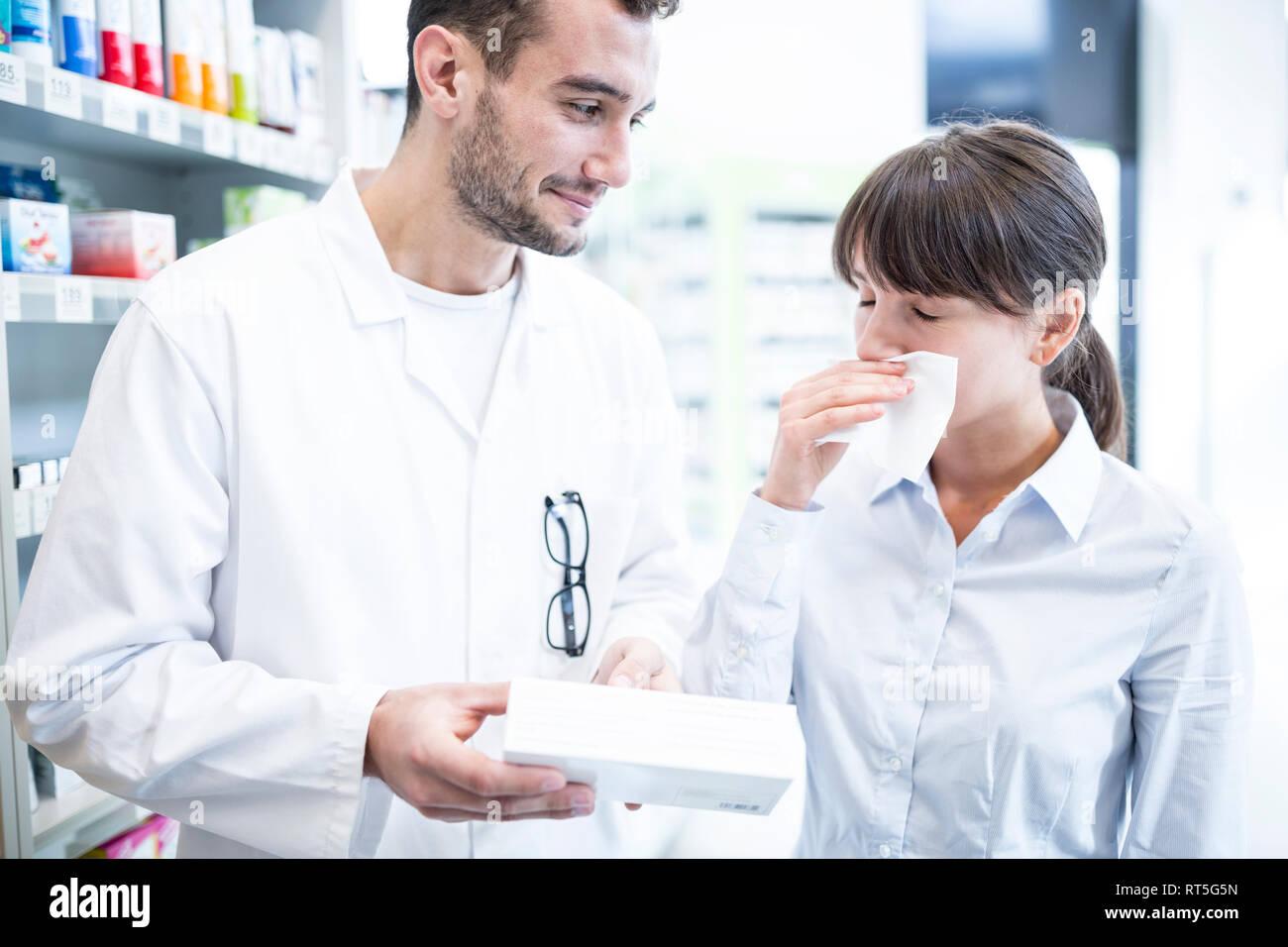 Pharmacist advising customer in pharmacy - Stock Image