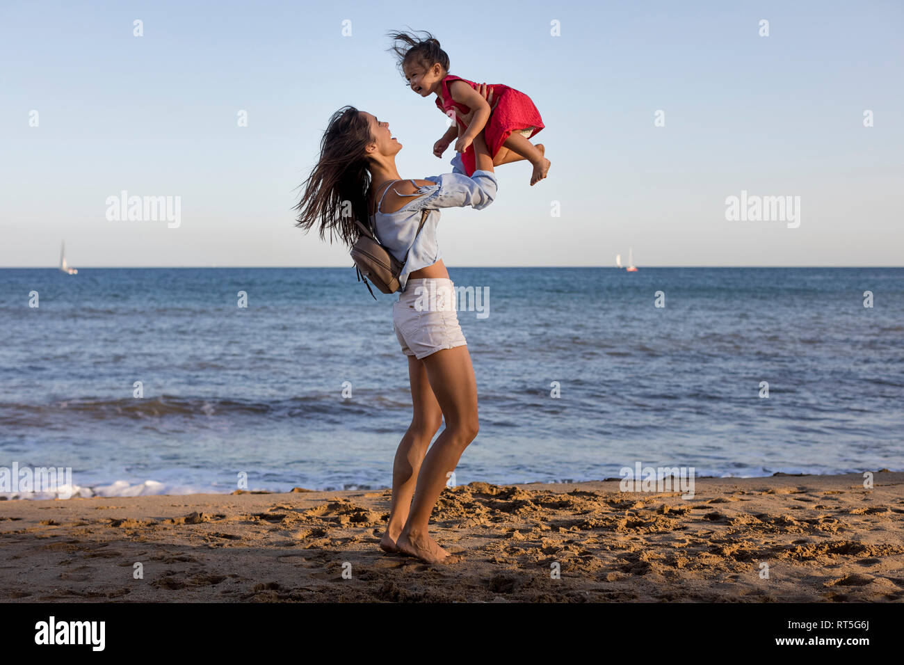 Mother and daughter having fun on the beach, pretending to fly Stock Photo