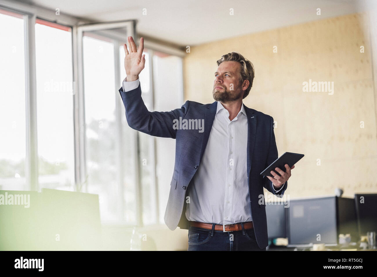 Businessman standing in office, holding digital talet, using his imagination - Stock Image