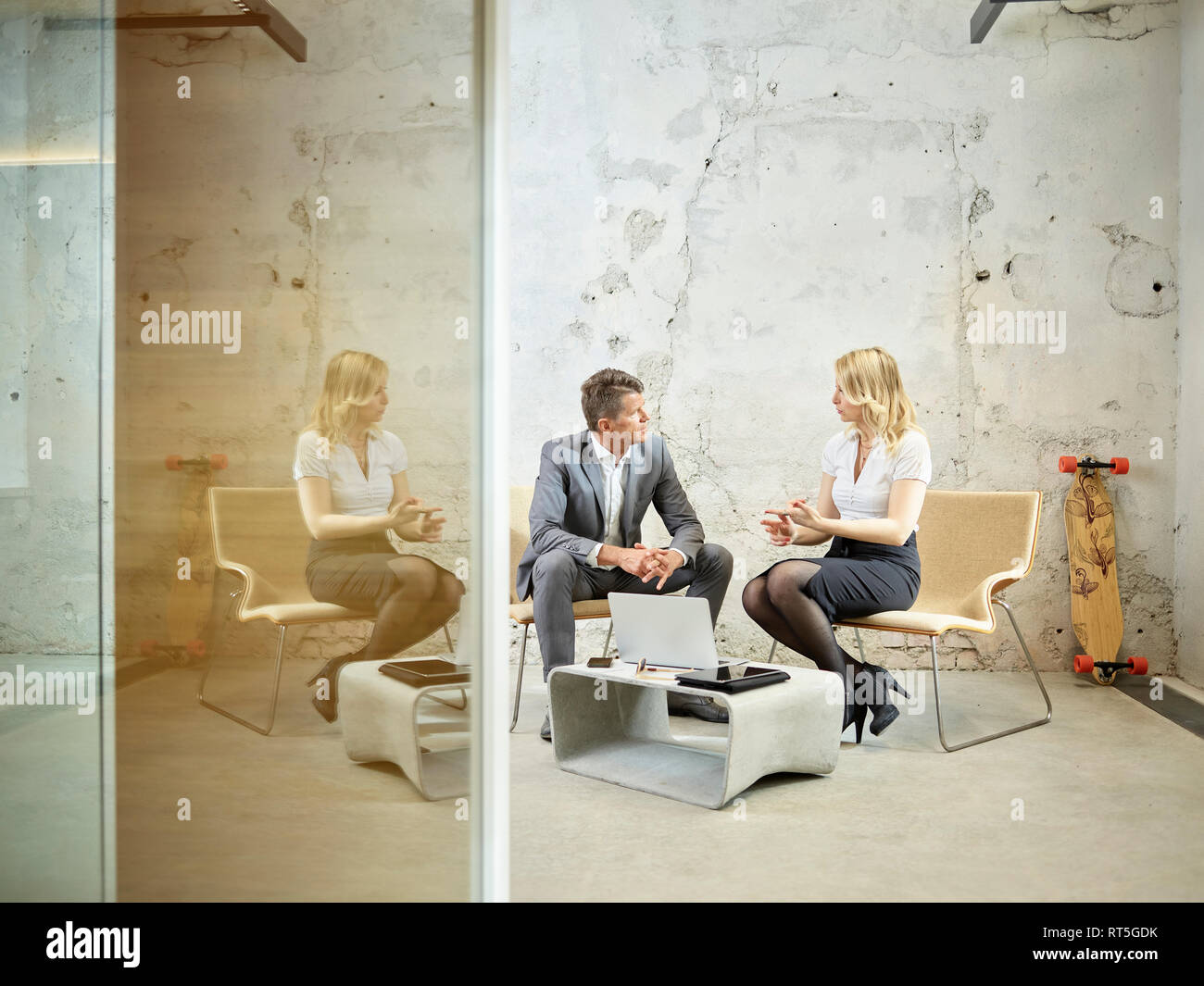 Businessman and businesswoman talking in modern office - Stock Image