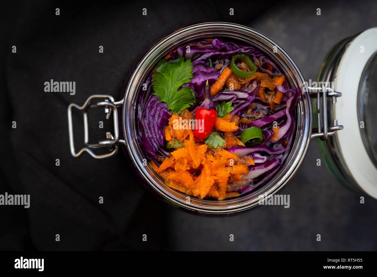 Homemade red cabbage, fermented, with chili, carrot and coriander, in a preserving jar - Stock Image