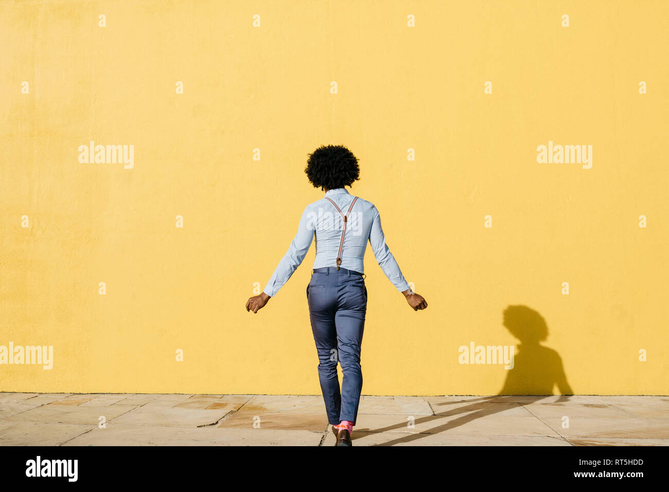 Back view of man wearing suspenders dancing in front of yellow wall - Stock Image