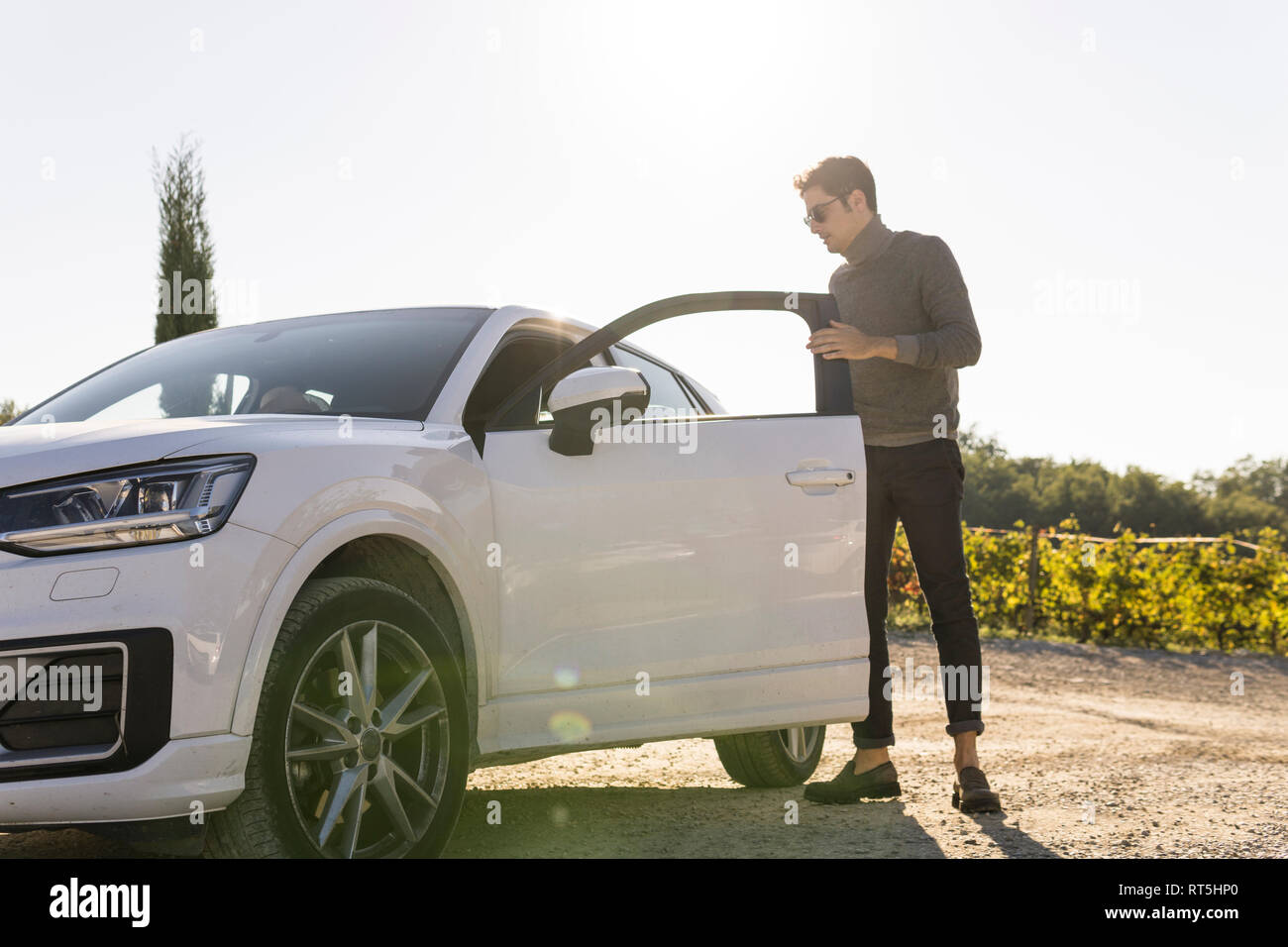 Italy, Tuscany, Siena, young man getting out of car in a vineyard - Stock Image