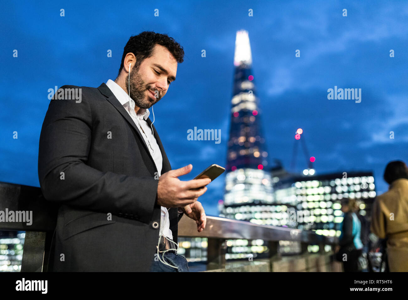 UK, London, businessman on the go checking his phone while commuting by night Stock Photo