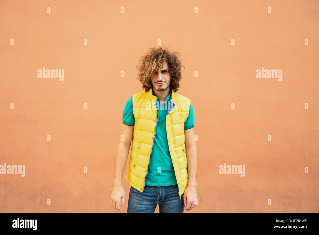 Portrait of annoyed young man with curly hair wearing yellow waistcoat outdoors - Stock Image