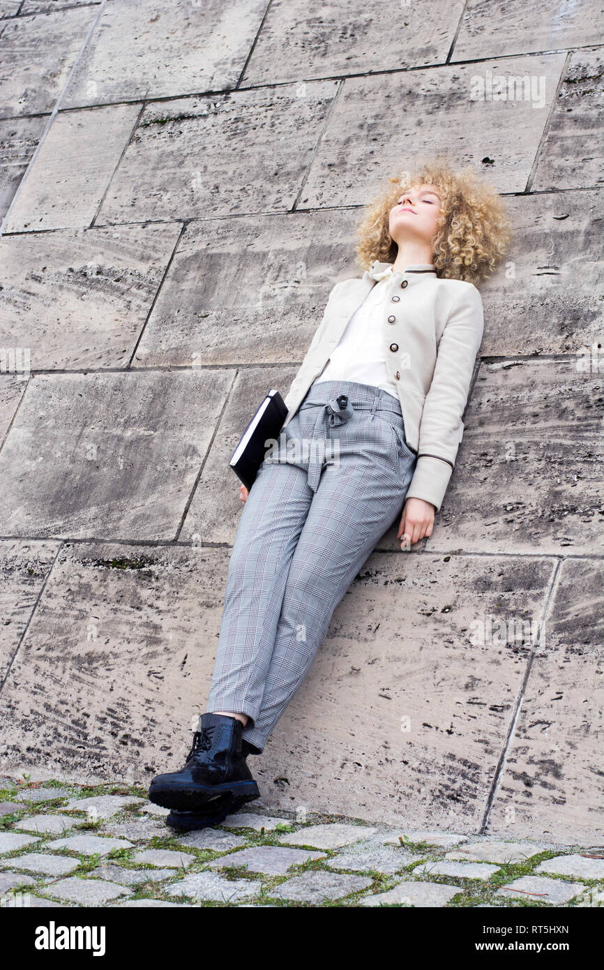 Fashionable blond woman with folder leaning against wall having a rest Stock Photo